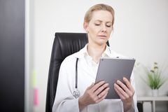 Woman Clinician Looking at Tablet Screen Seriously Royalty Free Stock Photo