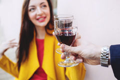 Woman clinking red wine glass with man outdoors Stock Images