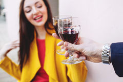 Woman clinking red wine glass with man outdoors Royalty Free Stock Photography