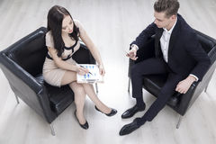 Woman with clipboard and man in armchair Stock Image