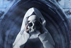 A woman in cloak with a human skull. A woman in white hooded cloak holding a human skull in front of her face on temple arch background royalty free stock photo