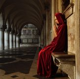 Woman in cloak outdoors. Woman in red cloak praying alone stock images