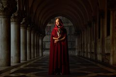 Woman in cloak outdoors. Woman with a mask wearing red cloak outdoor royalty free stock images