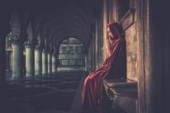 Woman in cloak praying. Woman in red cloak praying alone Royalty Free Stock Photo