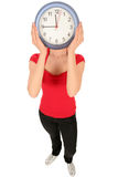 Woman with clock covering face Stock Image