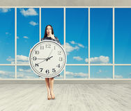 Woman with clock in empty room Royalty Free Stock Photo