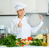 Woman with clock at kitchen Royalty Free Stock Image