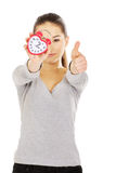 Woman with a clock and thumbs up. Royalty Free Stock Image