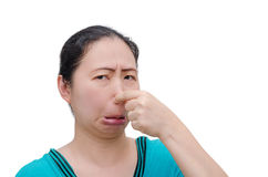 Woman close her nose from bad smell. Asian woman close her nose from bad smell over white background royalty free stock photo