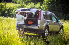 Woman close the suv in countryside Stock Image