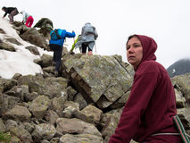 Woman close up with disturbing face. Against the background of tourists climb the mountain Stock Photography
