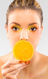 Woman close up with a orange slice Stock Photography