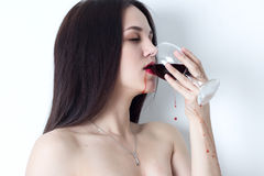 Woman with closed eyes drinking red wine, which sprinkles on both sides Royalty Free Stock Image