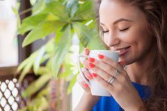 Woman with closed eyes enjoying a cup of coffee Stock Image