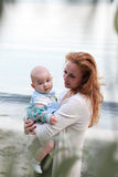 Woman with closed eyes holding a baby in her arms Stock Image