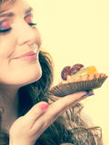 Woman closed eyes holds cake in hand Royalty Free Stock Photo