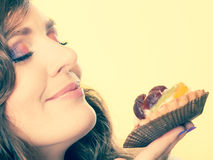 Woman closed eyes holds cake in hand Stock Photography