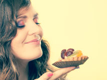 Woman closed eyes holds cake in hand Royalty Free Stock Photos