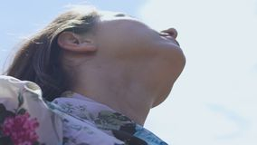 Woman with closed eyes lifting head up to sky praying, looking at skies slow