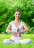 Woman with closed eyes in lotus position prayer gesturing Stock Photo