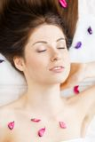 Woman with closed eyes lying in petals of flowers Royalty Free Stock Photography