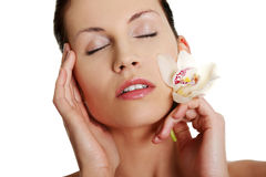 Woman with closed eyes and orchid flower. Royalty Free Stock Photography
