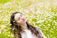 Woman with closed eyes relaxes in daisies Stock Images