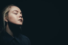 Woman with closed eyes. Sad woman with closed eyes on black background Royalty Free Stock Photos