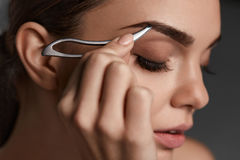 Woman With Closed Eyes And Tweezers For Eyebrows. Beauty Tools Royalty Free Stock Image
