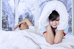 Woman closed her ears on bed Stock Images