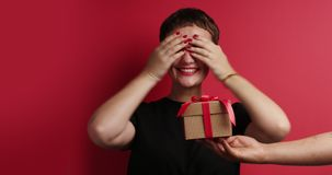 Woman closed her eyes to receive a gift box and happy to see it then. Rolling and watching at stock video
