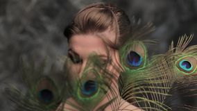 The woman is closed with the peacock feathers stock footage