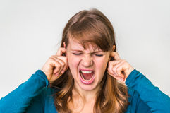 Woman closes ears with fingers to protect from loud noise. On white Stock Photo