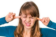 Woman closes ears with fingers to protect from loud noise. Isolated on white Royalty Free Stock Photography