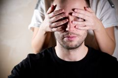 A man looks through the fingers of a woman who covers his face with his hands