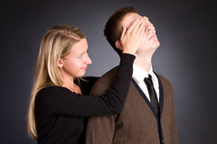 The woman closes hands behind an eye of the men. Royalty Free Stock Photography