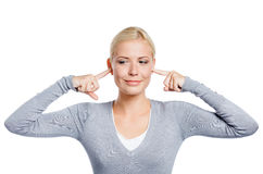 Woman closes her ears with fingers Stock Image