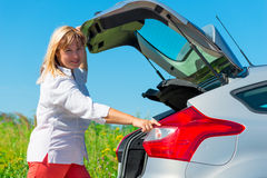 Woman closes the trunk of the car Stock Photo