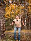 The woman closeup looks up and ready to jump. On the forest background Stock Images