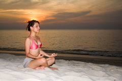 Woman closing eyes doing yoga on the beach Royalty Free Stock Photography