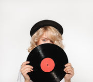 Woman closing face with vinyl record. Studio shot of young blond woman looking at camera closing face with the vinyl royalty free stock photos