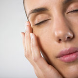 Woman closing her eyes. A studio closeup of a beautiful woman's face with eyes closed Stock Photos