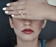 Woman closing her eyes with her hand. Woman closing her eyes with hand Royalty Free Stock Photography