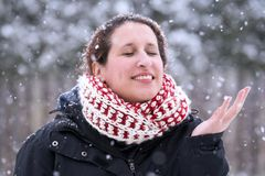 Woman closing her eyes and smiling with hand up as snow falls ge Stock Photos