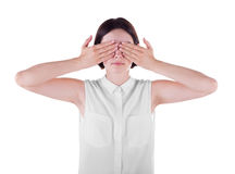 A woman closing her face with both hands. A casual and scared young lady isolated over the white background. Misunderstanding. Stock Image