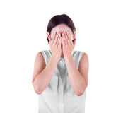 A woman closing her face with both hands. A casual and scared young lady isolated over the white background. Misunderstanding. royalty free stock image