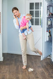 Woman closing refrigerator door while carrying baby girl Stock Photo