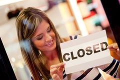 Woman closing a retail store Stock Images