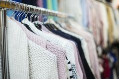 Woman clothes on hangers in textile store on sale. Stock Photos
