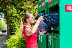 Woman at clothes recycling skip Stock Photography